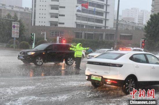 图为保定市公安交警在大雨中疏导交通。 保定市交警支队供图