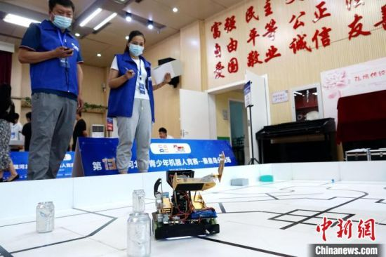 图为比赛现场,两名裁判员现场监测机器人比赛数据。 李佳新 摄