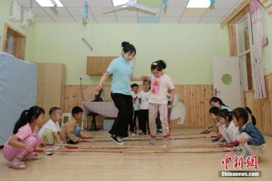 资料图:老师带领孩子们在教室内游戏。中新社记者 张远 摄