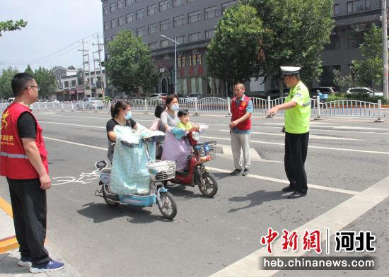 志愿者协助交警劝导不文明交通行为。 张明月 摄