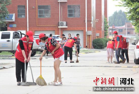 志愿者在清扫小区路面垃圾。 张明月 摄