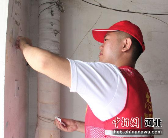 志愿者在清理楼道小广告。 张明月 摄