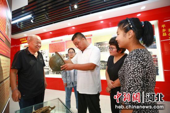 张会申(左一)在军事国防教育展馆进行讲解。 柴更利 摄