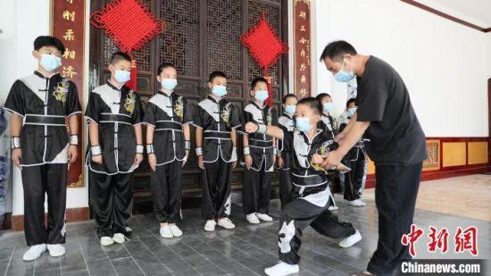 李秀志(右一)指导学生们练习武术动作。 田威 摄