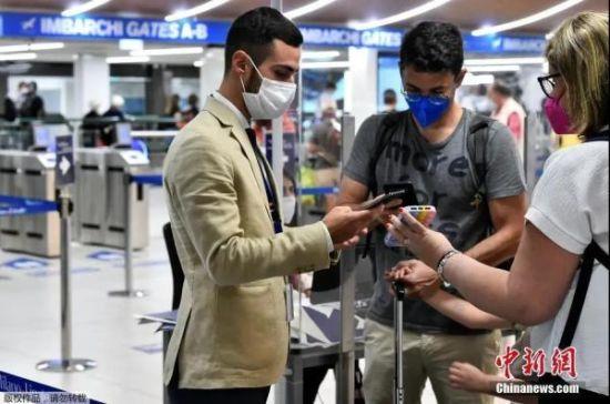资料图:意大利米兰,工作人员在机场检查乘客的绿色通行证。