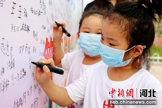 2021年9月3日,签字墙前一对双胞胎姐妹同时入学签字。 刘巨雷 摄