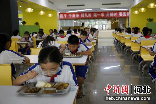 学生们在享用免费营养午餐。 张鑫 摄