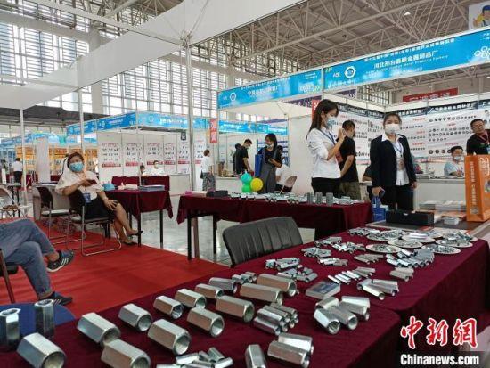 图为展览会上,一名参展商展出不同型号的标准件。 王天译 摄