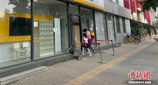 北京市中关村,家长送孩子进辅导班。 任靖 摄