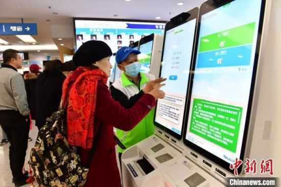 资料图:患者在指导下使用人脸识别系统预约专家号。(图文无关) 王广兆 摄