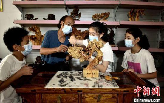 张国印指导临城县石城小学学生制作根雕。 宋继昌 摄
