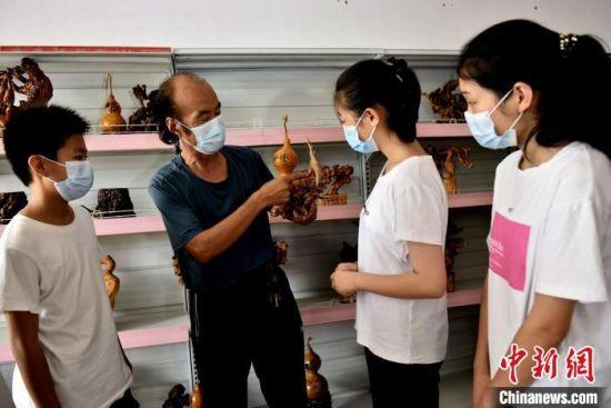 张国印向临城县石城小学学生讲解根雕工艺。 宋继昌 摄