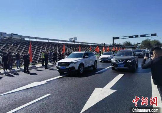 图为开通仪式后首批驶过燕郊出口立交枢纽的车辆。 宋敏涛 摄