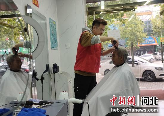 图为高阳志愿者免费为当地老年人理发。 杨�� 摄